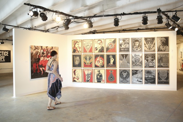 MIAMI, FL - DECEMBER 03: An attendee views artwork at The Dean Collection X BACARDI No Commission Art Fair Day 1 on December 3, 2015 in Miami, Florida. (Photo by Monica Schipper/Getty Images for Bacardi)