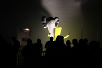 People dancing in front of a Kaws sculpture from The Dean collection.